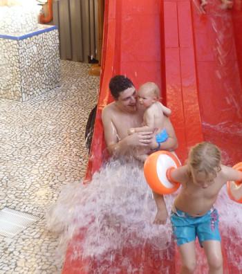 Mila rutscht mit Papa auf der Wasserrutsche.