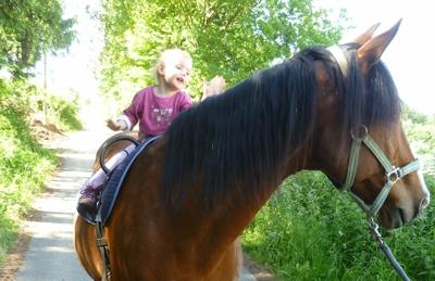 Mila reitet mit Voltigiergurt.
