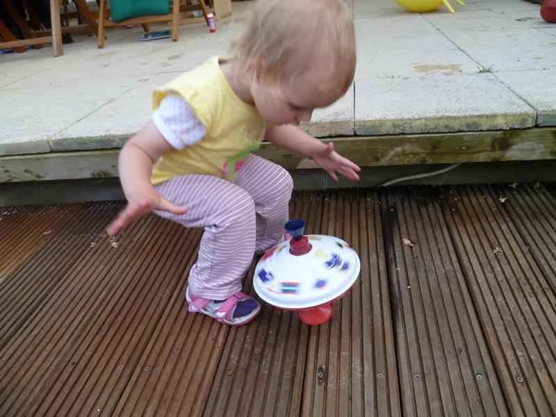 Mila spielt mit einem Brummkreisel