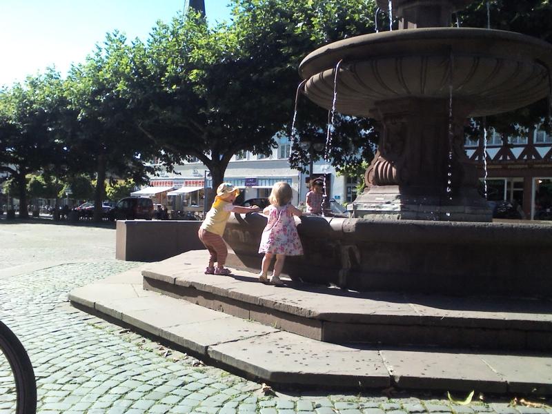 Mila spielt am Brunnen in Holzminden