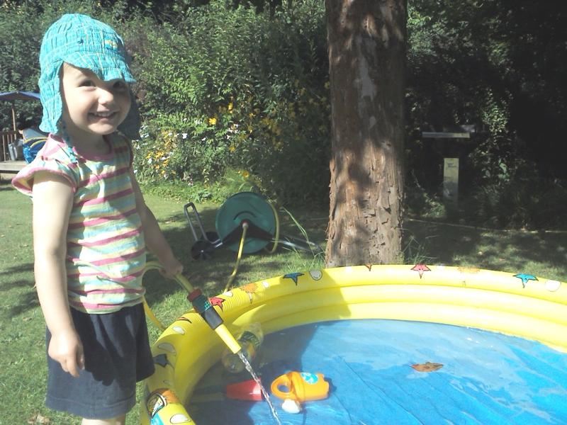 Mila füllt Wasser in ihr Planschbecken.