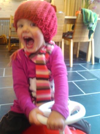 Mila mit Mütze auf dem Bobbycar