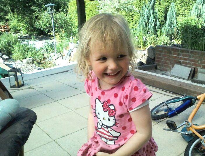 Mila lacht im Garten.
