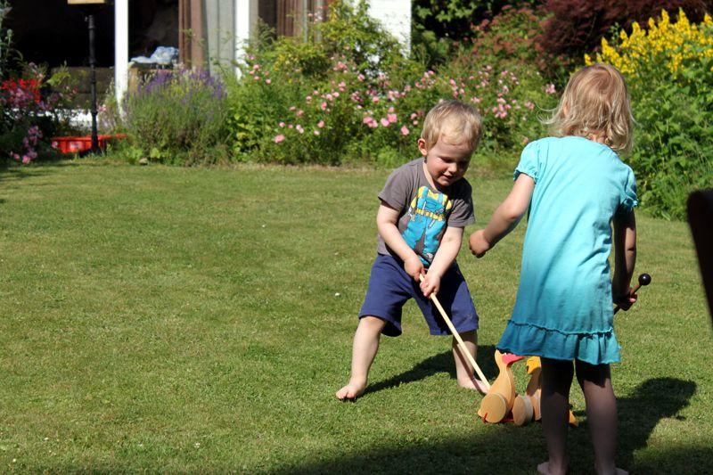 Mila und Eliah spielen mit Enten Hockey.